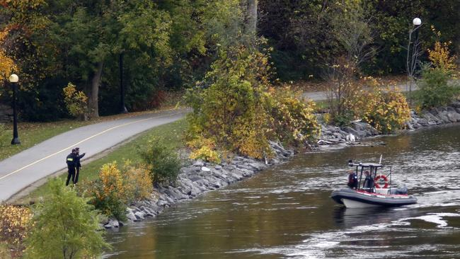 Manhunt ... A police boat searches behind Parliament Hill in Ottawa late on Wednesday.