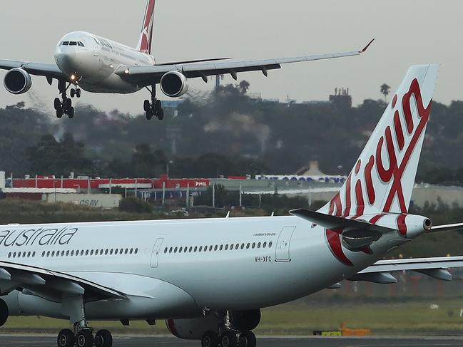 An Airbus SE A330-300 aircraft operated by Qantas Airways Ltd., top, approaches to land as aircraft operated by Qantas's low-cost unit Jetstar Airways, left, and Virgin Australia Holdings Ltd. stand on the tarmac at Sydney Airport in Sydney, Australia, on Tuesday, Feb. 20, 2018. Qantas reports first-half results on Feb. 22 and has said profit may rise as much as 12 percent. Photographer: Brendon Thorne/Bloomberg