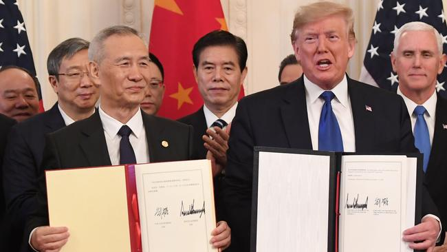 Chinese Vice Premier Liu He and US President Donald Trump display the signed trade agreement between the US and China in the East Room of the White House in Washington, DC. (Photo by SAUL LOEB / AFP)