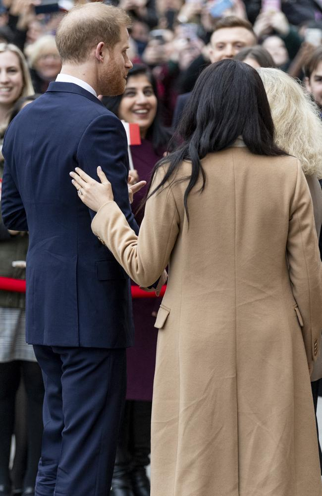 Meghan places her hand on Harry's back as they greet fans. Picture: Mark Cuthbert/UK Press via Getty Images