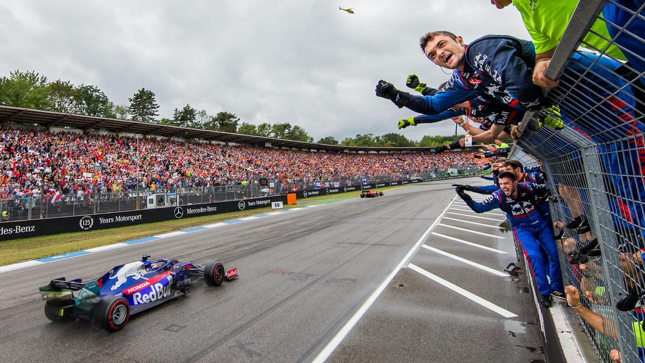 Toro Rosso crew members celebrate as Kvyat crosses the line.