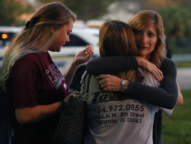 Kristi Gilroy (R), hugs a young woman at a police check point near the Marjory Stoneman Douglas High School where 17 people were killed. Picture: Getty