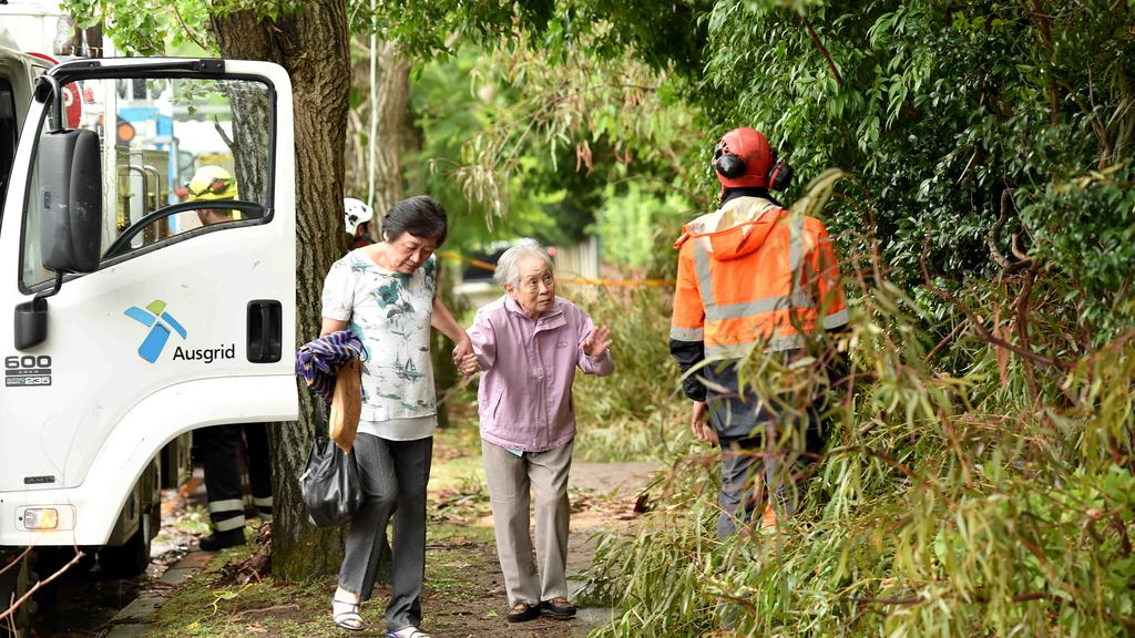 Pedestrians walk through the mess as Ausgrid workers mop up and try to restore power after a fallen tree. Picture: AAP IMAGE / Troy Snook