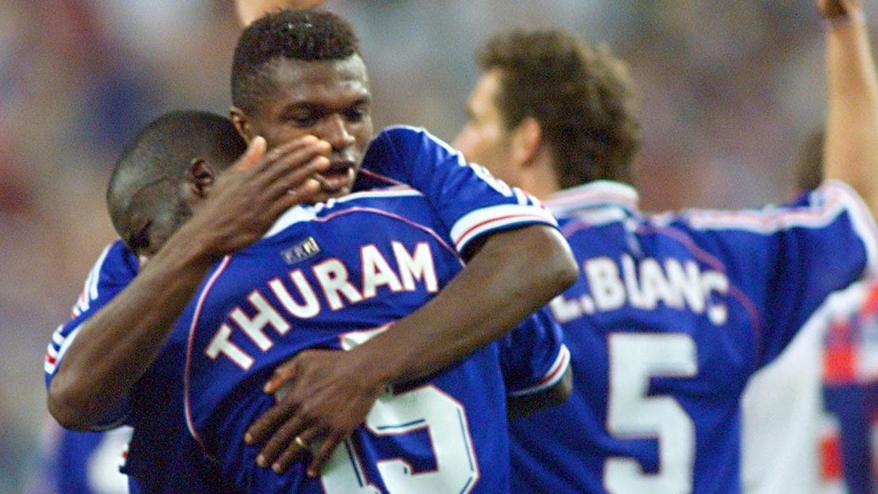 French defender Marcel Desailly (2nd L) hugs teammate Lilian Thuram (foreground) as Laurent Blanc (#5) raises his arms after Thuram scored a goal for his team during the Soccer World Cup semi-final match France vs Croatia