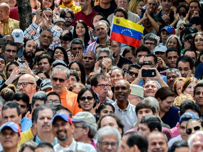 "Opposition supporters listen to Venezuela's National Assembly head and the country's self-proclaimed ""acting president"" Juan Guaido, at Bolivar Square in Chacao, eastern Caracas. Picture: Luis Robayo"