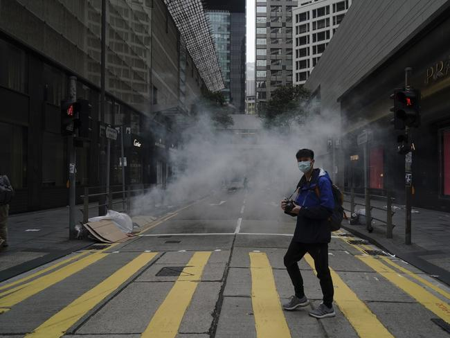 A man walks past as police use tear gas on protesters during a violent anti-government protest on Sunday. Picture: AP Photo/Kin Cheung