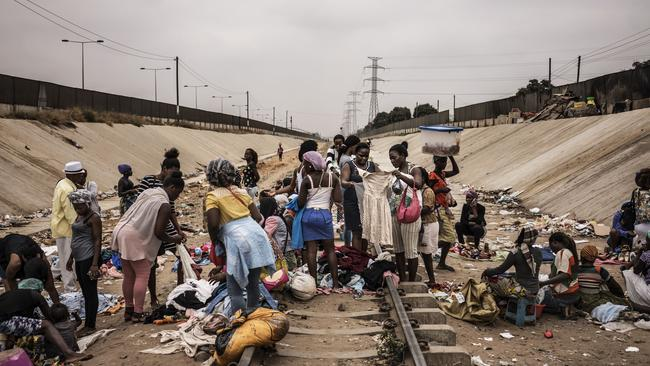 Hawkers sell their products in an improvised market across a train track in the Viana district in Luanda. Picture: Marco Longari/AFP