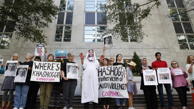 People hold signs at the Embassy of Saudi Arabia in the US during protest about the disappearance of Saudi journalist Jamal Khashoggi.