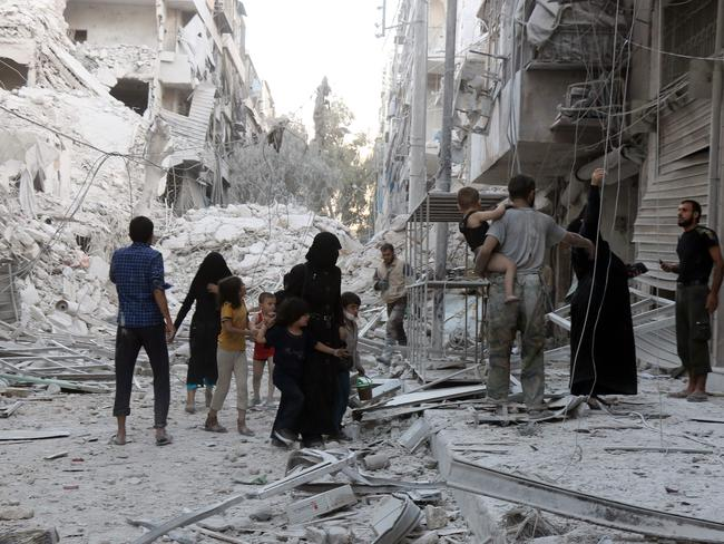 This is also Aleppo, where a young family is fleeing from the al-Muasalat district following air strikes on September 23, 2016. Picture: AFP/Thaer Mohammed