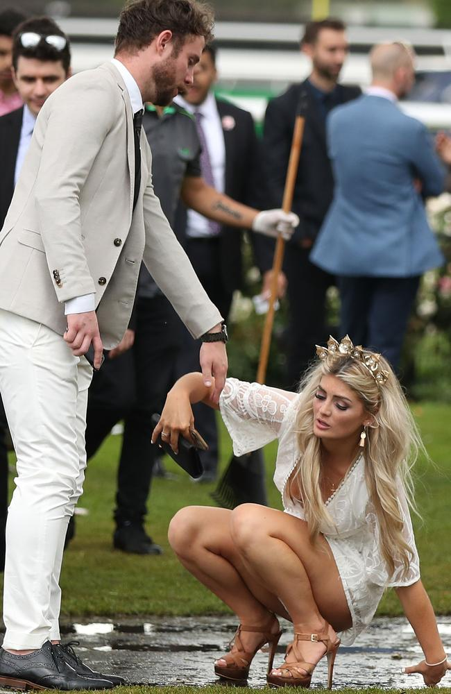 A reveller graciously recovers after slipping in the wet as she makes her way home from Flemington Racecourse. Elsewhere in Australia the scenes were more wild. Picture: Scott Barbour/Getty Images