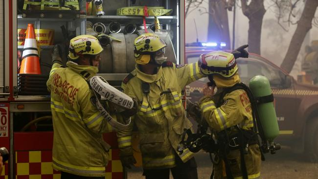 Firefighters work to save a house in Possum Brush, south of Taree. Picture: AAP