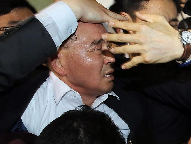 Focus of anger ... South Korean Prime Minister Chung Hong-won is shielded by his bodyguards at a shelter for relatives of passengers in Jindo, south of Seoul.