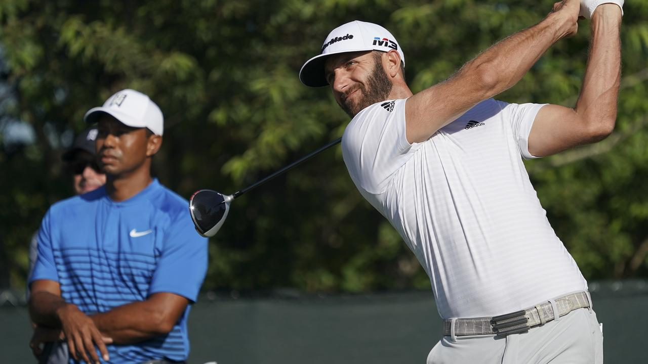 Dustin Johnson hits off the fourth tee as Tiger Woods.