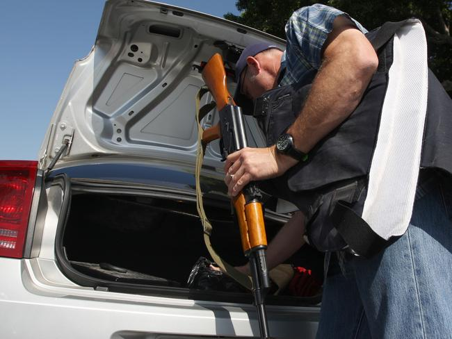 Baby steps ... a police officer removes a surrendered semiautomatic weapon and bulletproof vest from a car at a gun buyback event in Los Angeles in the wake of a killing spree at University of California, Santa Barbara. Gun attacks in US schools now occur at the rate of once per week.