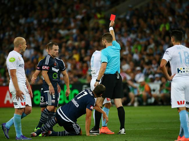 Melbourne City's Anthony Caceres sees red after a challenge on Melbourne Victory's Matthieu Delpierre.