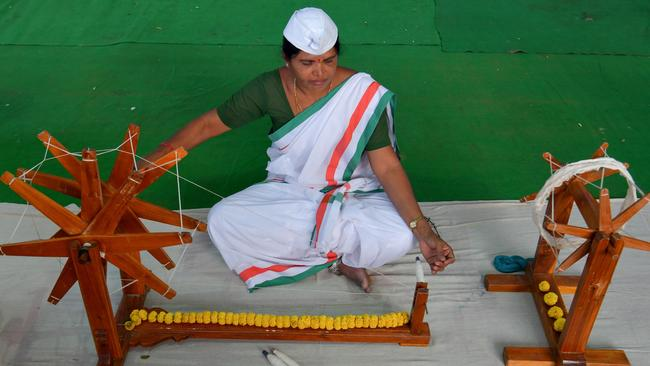 "An Indian weaver uses a ""Charaka"", traditional hand spinning weaving machine. Picture: AFP"