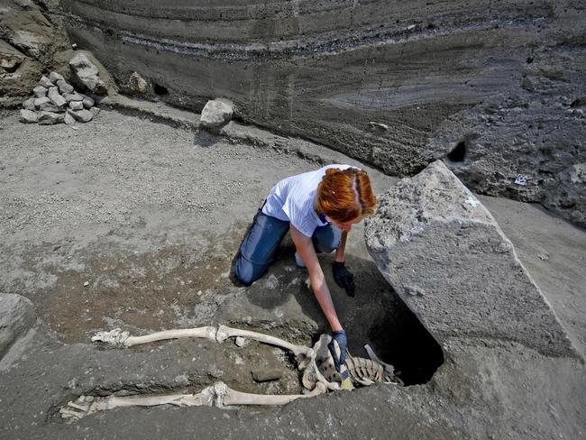Anthropologist Valeria Amoretti works with a brush on a skeleton of a victim of the eruption of Mt. Vesuvius in A.D. 79, which destroyed the ancient town of Pompeii. Picture: Ciro Fusco/ANSA via AP