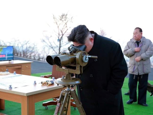 In this March 6, 2017, photo distributed by the North Korean government, leader Kim Jong Un looks through a scope at an observation point to watch the launching of Scud missiles in Tongchang-ri in North Pyongan Province, North Korea. Picture: AP