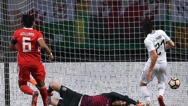 TOPSHOT - Wales' goalkeeper Wayne Hennessey (C) fails to save the ball for a goal by Uruguay's Edinson Cavani (R)