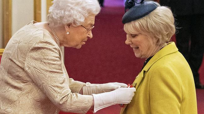 Queen Elizabeth paired her cream ensemble with white gloves today as she honoured actress Wendy Craig. Picture: PA via AP.