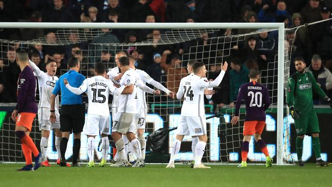 Swansea players protest to referee Andre Marriner over the penalty. Picture: Getty