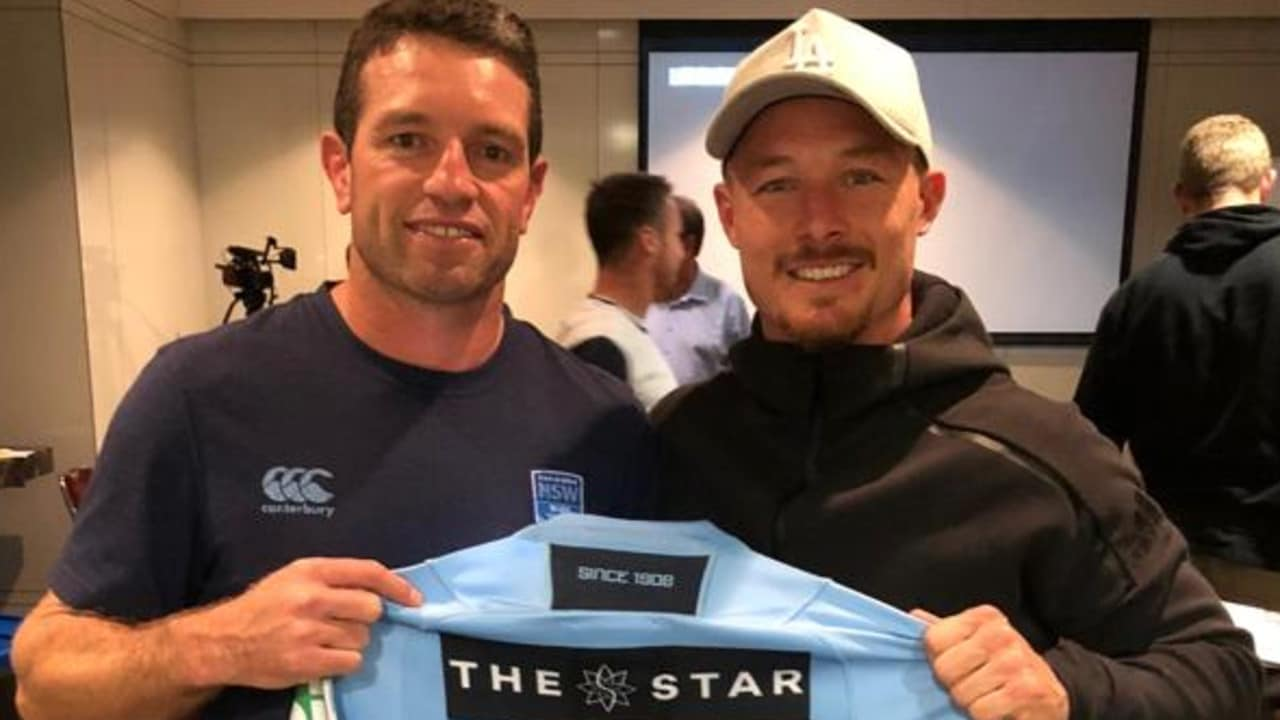 Danny Buderus presents Damien Cook with his Blues jersey.