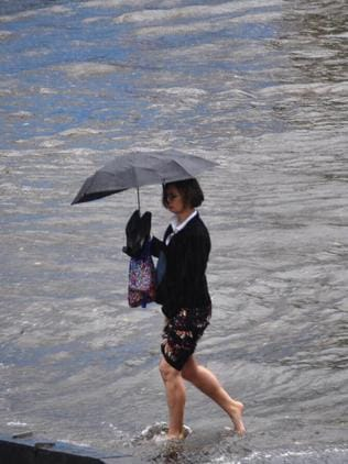 A woman braves floodwater on Commercial Rd. Picture: Alexandra Owen
