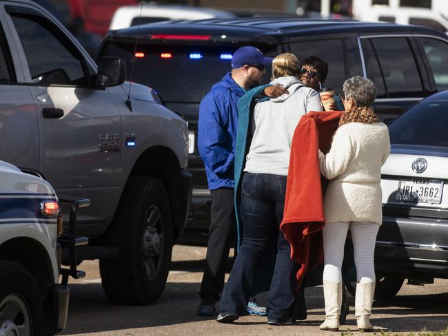 Residents embrace near police and fire cars that surround the scene of a shooting at a Texas church. Picture: AP