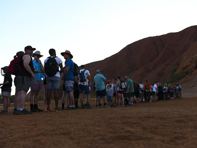 Tourists are seen lining up to climb Uluru ahead of a ban that takes effect on Saturday. Picture: AAP Image/Lukas Coch