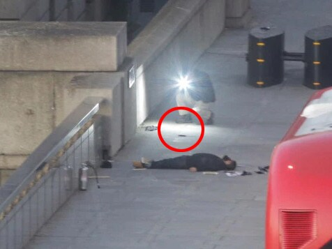 This is the suspect lying on London Bridge and the red circle shows the knife that was duct-taped to his hand. Picture: Cliff Hide/The Times
