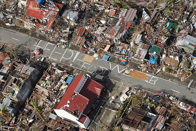 An aerial view shows signs for help and food amid the destruction left from Typhoon Haiyan in the coastal town of Tanawan, central Philippines. (AP / Wally Santana)