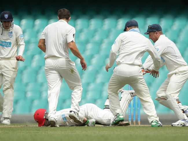 Hughes collapses in the middle of a group of NSW players.