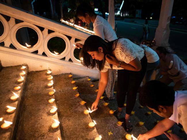 Mourners light candles for the victims. Picture: AFP