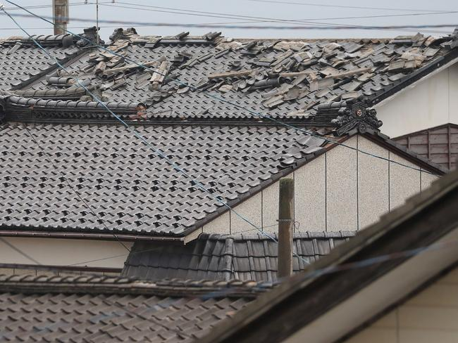 Roofs of homes showed bare spots where tiles had shaken loose. Picture: AFP