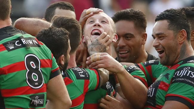Jason Clark of the Rabbitohs (centre) is congratulated after scoring a try.