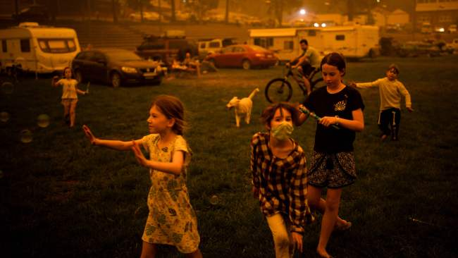 Children play at the showgrounds in the southern New South Wales town of Bega where they are camping after being evacuated from nearby sites affected by bushfires on Photo: SEAN DAVEY / AFP.