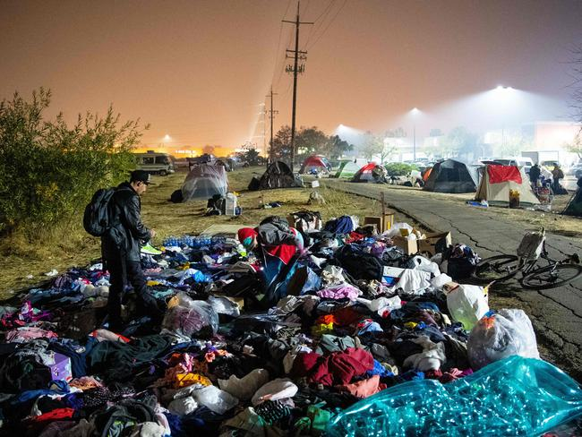 Evacuees sift through a pile of clothing at an evacuee encampment in a Walmart parking lot in Chico, California. Picture: AFP