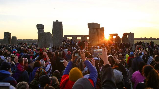Revellers watch the sunrise as they celebrate the pagan festival of Summer Solstice at Stonehenge in Wiltshire, southern England on June 21, 2018. The festival, which dates back thousands of years, celebrates the longest day of the year when the sun is at its maximum elevation. Modern druids and people gather at Stonehenge every year to see the sun rise on the first morning of summer. Picture: Geoff Caddick