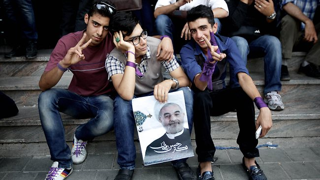 Iranians supporters of moderate presidential candidate, Hassan Rowhani flash the sign of victory holding a portrait of him as they wait for the final results outside his campaign headquarter in downtown Tehran on June 15, 2013. Rowhani has a clear lead in Iran's presidential election, garnering 51 percent of the vote at 65 percent of polling stations across the country, the interior ministry said. AFP PHOTO/BEHROUZ MEHRI