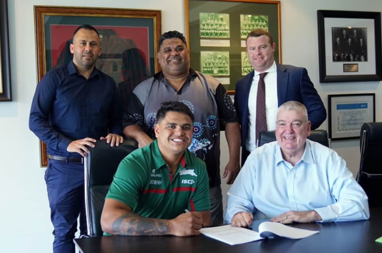 Latrell Mitchell signs with the Rabbitohs, flanked by his agent Matt Rose (back left).