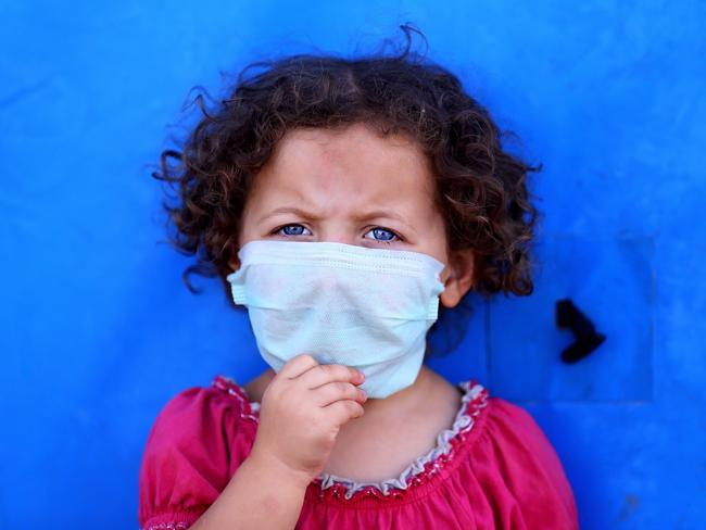 A young girl covers her mouth at a camp for displaced Iraqis in the Khazer area outside Irbil, northern Iraq, on Sunday.