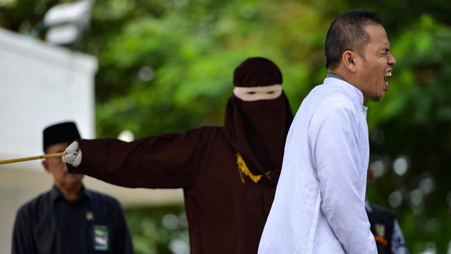 Mukhlis reacts as he is whipped in public by a member of the sharia police in Banda Aceh. Picture: AFP