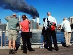 Pedestrians on the waterfront in Brooklyn, New York, look across the East River to the burning World Trade Center towers 11 September, 2001 after a terrorist attack. Picture: AFP PHOTO Henny Ray
