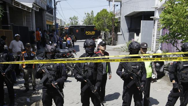 Police officers stand guard near the house of the family that carried the bombing of Surabaya police headquarters during a raid in Surabaya. Picture: AP