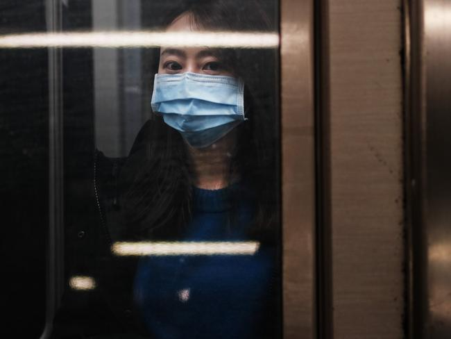 A woman wears a medical mask on the subway as New York City confronts the coronavirus outbreak. Picture: Getty