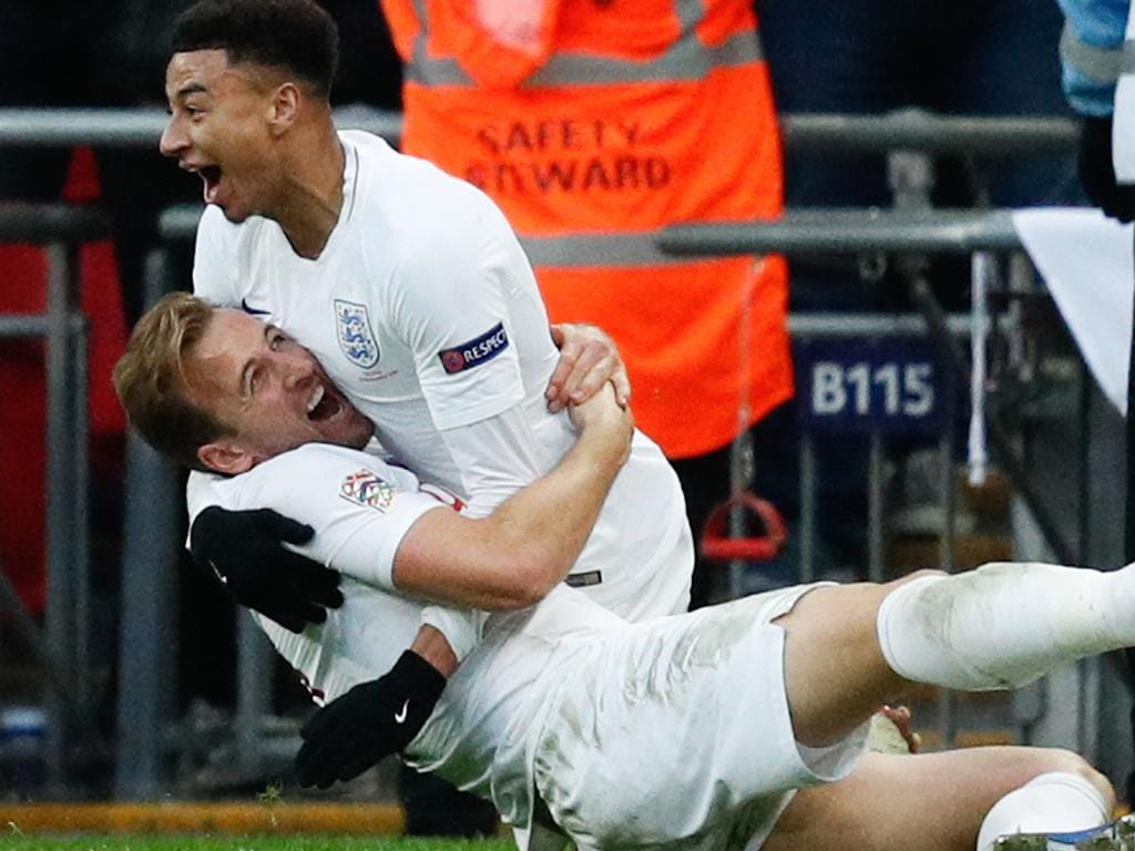 England's striker Harry Kane lies on the floor as England's midfielder Jesse Lingard (up) celebrates after Kane scores their second goal during the international UEFA Nations League football match between England and Croatia at Wembley Stadium in London on November 18, 2018. (Photo by Adrian DENNIS / AFP) / NOT FOR MARKETING OR ADVERTISING USE / RESTRICTED TO EDITORIAL USE