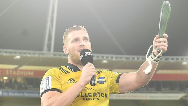 Hurricanes captain Brad Shields holds a pounamu mere to mark his 100th Super Rugby game.