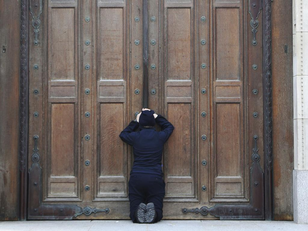 A woman prays at the closed doors of Westminster Cathedral in London, ahead of the Easter morning Mass. Picture: PA via AP