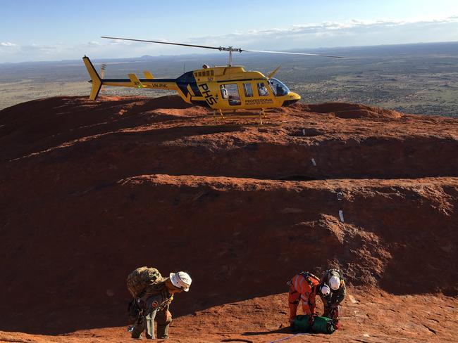 Three Australians were rescued after falling into a crevice on Uluru.