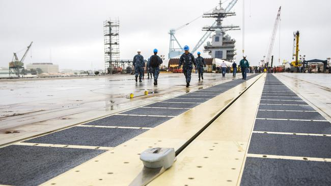 "Sailors from the future USS Gerald R. Ford walk the ship's flight deck following the first ""dead-load"" test of the ship's Electromagnetic Aircraft Launch System. (US Navy Photo by Mass Communication Specialist 1st Class Joshua J. Wahl/Released)"